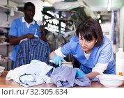 Купить «Female laundry worker during daily work», фото № 32305634, снято 15 января 2019 г. (c) Яков Филимонов / Фотобанк Лори