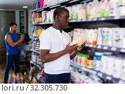 Купить «Athletic African looking for necessary food supplements», фото № 32305730, снято 18 февраля 2020 г. (c) Яков Филимонов / Фотобанк Лори