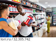 Купить «Confident African seller offering diet and sports supplements to interested athletic person in sports nutrition store», фото № 32305742, снято 30 марта 2020 г. (c) Яков Филимонов / Фотобанк Лори
