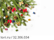 Купить «Christmas tree branch decorated with cones, snowflakes and bows on a white background», фото № 32306034, снято 19 октября 2019 г. (c) Юлия Бабкина / Фотобанк Лори