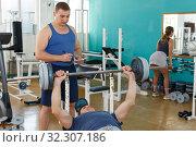 Купить «Man doing bench press with help of coach», фото № 32307186, снято 5 ноября 2018 г. (c) Яков Филимонов / Фотобанк Лори