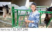 Купить «Smiling woman near enclosure with horses», фото № 32307246, снято 17 ноября 2019 г. (c) Яков Филимонов / Фотобанк Лори