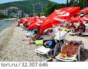 Купить «Budva, Montenegro - June 13.2019. City beach in the resort area with red umbrellas with Coca Cola brand», фото № 32307646, снято 13 июня 2019 г. (c) Володина Ольга / Фотобанк Лори