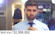 Man tying a tie at wear store. Стоковое видео, видеограф Илья Шаматура / Фотобанк Лори