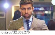 Man puts on a jacket at clothing store. Стоковое видео, видеограф Илья Шаматура / Фотобанк Лори