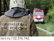 Купить «Firefighters of Fire Department of Federal Fire Service, back view with emblem Emercom of Russia on uniform rescuers of Ministry of Civil Defence, Emergencies and Disaster Relief of the Russian Federation (MChS)», фото № 32316742, снято 7 августа 2019 г. (c) А. А. Пирагис / Фотобанк Лори