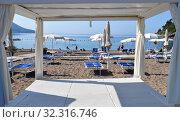 Купить «Becici, Montenegro - June 13.2019. City beach in the resort area with closed umbrellas», фото № 32316746, снято 11 июня 2019 г. (c) Володина Ольга / Фотобанк Лори