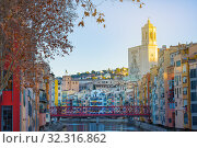 Colorful and houses and bridge Pont de Sant Agusti reflected in river Onyar, in Girona, Catalonia, Spain. Church of Sant Feliu and Saint Mary Cathedral at background in winter (2019 год). Редакционное фото, фотограф Papoyan Irina / Фотобанк Лори
