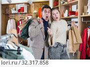 Купить «Smiling couple is satisfied of purchases and standing with package», фото № 32317858, снято 12 марта 2018 г. (c) Яков Филимонов / Фотобанк Лори