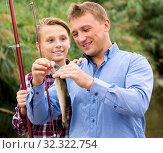 Купить «Man with teenager boy releasing fish from hook», фото № 32322754, снято 12 июля 2020 г. (c) Яков Филимонов / Фотобанк Лори