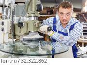 Купить «Man working on curved glass beveling machine», фото № 32322862, снято 10 сентября 2018 г. (c) Яков Филимонов / Фотобанк Лори