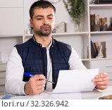 Купить «Young male struggling to pay utility bills and rent», фото № 32326942, снято 25 декабря 2017 г. (c) Яков Филимонов / Фотобанк Лори