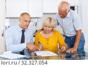 Elderly husband and wife signing agreement papers with bank worker. Стоковое фото, фотограф Яков Филимонов / Фотобанк Лори