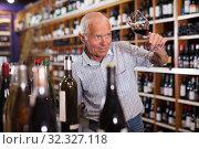 Купить «Man tasting wine in wine store», фото № 32327118, снято 8 мая 2019 г. (c) Яков Филимонов / Фотобанк Лори