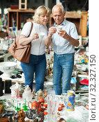 Купить «Pensioner family buys vintage dishes at a flea market», фото № 32327150, снято 11 мая 2019 г. (c) Яков Филимонов / Фотобанк Лори