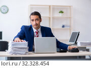Купить «Young male businessman sitting in the office», фото № 32328454, снято 20 июня 2019 г. (c) Elnur / Фотобанк Лори