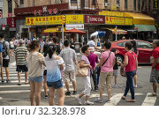 Pedestrians crown Bowery at Chatham Square in Chinatown in New York on Saturday, August 3, 2019. Редакционное фото, фотограф Richard Levine / age Fotostock / Фотобанк Лори
