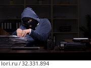 Купить «Male thief in balaclava in the office night time», фото № 32331894, снято 22 апреля 2019 г. (c) Elnur / Фотобанк Лори