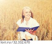 Купить «smiling young woman reading book on cereal field», фото № 32332670, снято 31 июля 2016 г. (c) Syda Productions / Фотобанк Лори