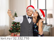 Купить «couple in santa hats taking selfie on christmas», фото № 32332710, снято 15 декабря 2017 г. (c) Syda Productions / Фотобанк Лори