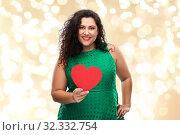 Купить «happy woman holding red heart over lights», фото № 32332754, снято 15 сентября 2019 г. (c) Syda Productions / Фотобанк Лори