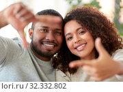 Купить «happy couple making selfie gesture at home», фото № 32332802, снято 22 сентября 2019 г. (c) Syda Productions / Фотобанк Лори