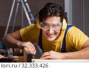 Купить «Worker working in repair workshop in woodworking concept», фото № 32333426, снято 11 августа 2017 г. (c) Elnur / Фотобанк Лори