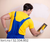 Купить «Young contractor employee applying plaster on wall», фото № 32334802, снято 15 марта 2018 г. (c) Elnur / Фотобанк Лори