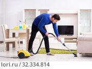 Купить «Young man vacuum cleaning his apartment», фото № 32334814, снято 13 марта 2018 г. (c) Elnur / Фотобанк Лори