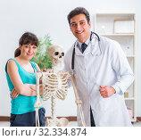 Купить «Doctor showing type of injury on skeleton to patient», фото № 32334874, снято 28 февраля 2018 г. (c) Elnur / Фотобанк Лори