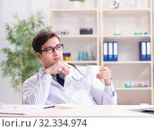 Купить «Young doctor sitting in the office», фото № 32334974, снято 15 февраля 2018 г. (c) Elnur / Фотобанк Лори