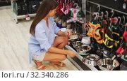 Купить «Caring young woman choosing accessories for her puppy in petshop», видеоролик № 32340286, снято 3 июня 2020 г. (c) Яков Филимонов / Фотобанк Лори