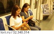 Купить «Two young women standing in subway car, surprised to look at screen of mobile phone», видеоролик № 32340314, снято 23 сентября 2019 г. (c) Яков Филимонов / Фотобанк Лори
