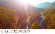 Купить «Mid air flight over fresh mountain river and meadow at sunny summer morning. Rural dirt road below.», видеоролик № 32340570, снято 29 мая 2017 г. (c) Александр Маркин / Фотобанк Лори
