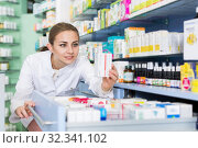 Купить «Young woman pharmacist is attentively looking medicines in apothecary», фото № 32341102, снято 26 марта 2018 г. (c) Яков Филимонов / Фотобанк Лори