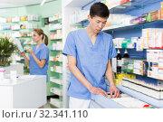 Купить «Man pharmacist is searching medicines on shelves», фото № 32341110, снято 26 марта 2018 г. (c) Яков Филимонов / Фотобанк Лори