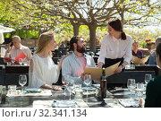 Charming young waiter and couple at open-air restaurant summer. Стоковое фото, фотограф Яков Филимонов / Фотобанк Лори