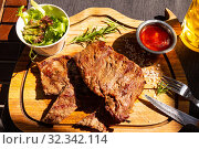 beautiful Tasty rump beef steak lies on cutting board stand along with fresh salad, a glass light beer, BBQ sauce and a sprig of rosemary. Table on terrace in restaurant in sunny summer day. Top view. Стоковое фото, фотограф Алексей Ширманов / Фотобанк Лори