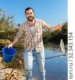 Купить «Adult man standing near river and pulling fish expressing emotions of dedication», фото № 32343154, снято 15 марта 2019 г. (c) Яков Филимонов / Фотобанк Лори