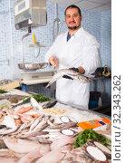 Купить «Seller holding fish», фото № 32343262, снято 27 октября 2016 г. (c) Яков Филимонов / Фотобанк Лори