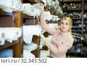 Купить «Woman looking for cloth in shop», фото № 32343502, снято 2 марта 2018 г. (c) Яков Филимонов / Фотобанк Лори