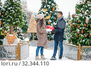 Young beautiful cheerful couple celebrating Christmas in the city street and giving gift to each other. Стоковое фото, фотограф Дмитрий Травников / Фотобанк Лори