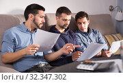 Three serious men discussing documents on sofa. Стоковое фото, фотограф Яков Филимонов / Фотобанк Лори