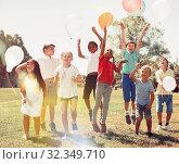 Купить «Friendly kids with balloons jumping together in park on summer», фото № 32349710, снято 7 июля 2020 г. (c) Яков Филимонов / Фотобанк Лори