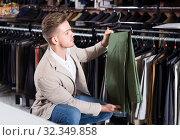 Купить «male customer examining trousers in men's cloths store», фото № 32349858, снято 9 декабря 2019 г. (c) Яков Филимонов / Фотобанк Лори