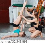 Купить «Sporty young woman exercising pole dance moves with trainer in fitness studio», фото № 32349898, снято 10 мая 2018 г. (c) Яков Филимонов / Фотобанк Лори