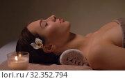 Купить «young woman lying at spa or massage parlor», видеоролик № 32352794, снято 19 октября 2019 г. (c) Syda Productions / Фотобанк Лори