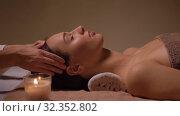 Купить «woman having face and head massage at spa», видеоролик № 32352802, снято 19 октября 2019 г. (c) Syda Productions / Фотобанк Лори