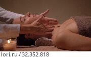 Купить «woman having face and head massage at spa», видеоролик № 32352818, снято 19 октября 2019 г. (c) Syda Productions / Фотобанк Лори