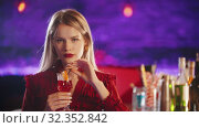 Купить «Gorgeous blonde young woman sitting by the bartender stand - drinking a beverage from the straw and looking in the camera», видеоролик № 32352842, снято 19 февраля 2020 г. (c) Константин Шишкин / Фотобанк Лори